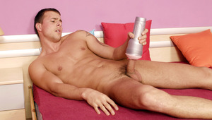 Joey Visconti on a bed, having fun with his new flesh jack!