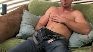 Appealing brunette gay Johnny rubbing his huge phallus on the couch