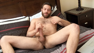 Tommy tweaks his nipples & beats his massive thick penis in bed