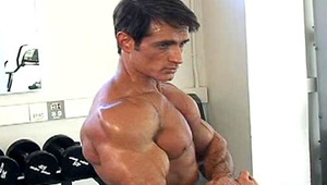 Very awesome stud exercising and lifting weights in a gym