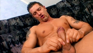 Tattooed lover wanking on a couch and sperm all over himself