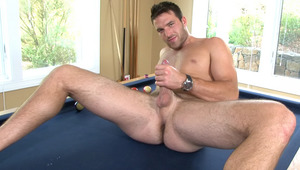 The charming buddy strokes his piece of wood on a pool table!