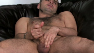 Hefty brunette gay Dj masturbating his giant dick on the couch